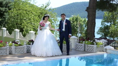 The bride and groom standing by the pool Arkistovideo