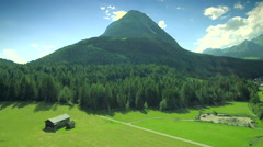Beautiful green grass mountain blue sky meadow forest landscape Austria aerial Stock Footage