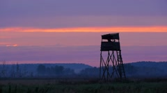 Hunting tower against clouds in a sunset light, man climbs into it Stock Footage