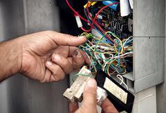Electrician repairing electric system Stock Photos