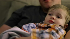 Little boy sitting on his dad's lap on the couch and being fussy Stock Footage