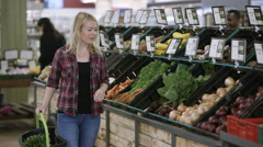 4K Young woman shopping for vegetables at the grocery store Stock Footage