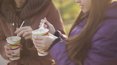 Mother and daughter drinking lattes in the autumn park. Soft sunlight. Mom tries Stock Footage