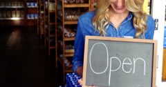 Smiling owner holding open signboard in supermarket Stock Footage