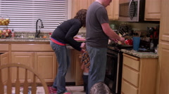 A father makes dinner while a mother undresses their little boy Stock Footage
