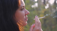 Close up of Young woman smoking a cigarette outdoor in slow motion coughing Stock Footage