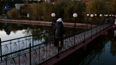 The fall, an elderly couple walking on the bridge with a cat. Stock Footage