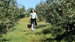 Teen girl walking with basket of apples in orchard Stock Footage