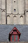 Red wooden dormer window on cathedral in bruges Stock Photos