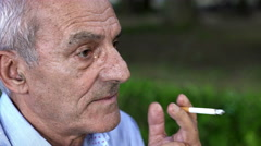 Thoughtful older man smokes a cigarette in the park Stock Footage