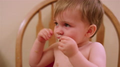 Little boy in a high chair booster seat eating messy food with his hands Stock Footage
