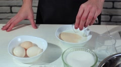 Woman pours the yeast in the milk. For the dough Stock Footage