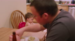 Little boy in a high chair booster seat eating messy food Stock Footage