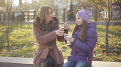Funny Mom and daughter drink latte and cocoa in the autumn park. Soft sunlight Stock Footage