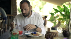 Young man adding brown sugar to coffee during breakfast, 4K Stock Footage