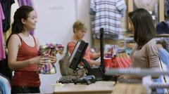 4K Customer in clothing store paying for a purchase with her credit card Stock Footage