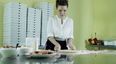 Cooking pizza. A young pretty woman kneading dough and preparing pizza base. HD Stock Footage