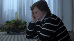 Profile of elderly woman worried sitting at a table Stock Footage