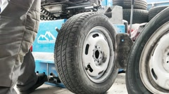 Mechanic using tire mounting tool machine. Car repair garage. Man Mount Tire On Stock Footage