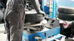 Mechanic using tire mounting tool machine. Car repair garage. car maintenance Stock Footage