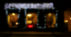 A cafe on the other side of a road with bright white flashing Christmas light Stock Footage