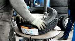 Man put on tyre on car wheel by special tool, mechanic using tire mounting tool Stock Footage
