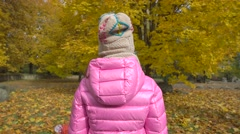 Girl in autumn park ape dressed in bright clothes. Stock Footage