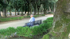 old man alone on a bench in a park Stock Footage