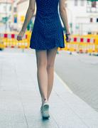 Pretty girl with long hair wearing a short dress in the city. Toned photo. Yo Stock Photos