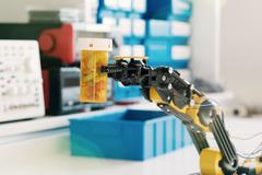 Plastic model of industrial robotics arm Robot manipulator and vial with pill Stock Photos