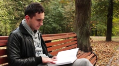 Man reading a book sitting on the bench Stock Footage