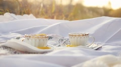 Tea cups outdoors at picnic during autumn with bokeh and sunshine in slowmotion Stock Footage