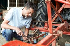 Farmer Working On Agricultural Equipment In Barn Stock Photos