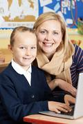 Teacher Helping Female Elementary School Pupil In Computer Class Stock Photos