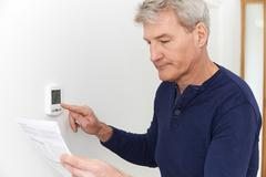 Worried Mature Man With Bill Turning Down Heating Thermostat Kuvituskuvat