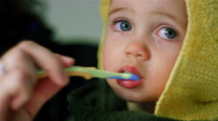 Adorable little boy wrapped in a towel as his mom brushes his teeth, Stock Footage