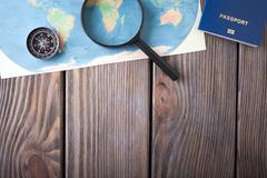 Preparation for Traveling concept, passport, compass, map on a wooden background Stock Photos