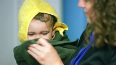 Adorable little boy wrapped in a towel as his mom dries off his face Stock Footage
