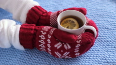 Female hands in red mittens holding a mug of tea Stock Footage