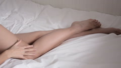 Nude female legs young girl lying in a white bed Stock Footage