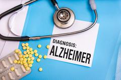 Alzheimer word written on medical blue folder with patient files, pills and s Stock Photos