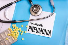 Pneumonia word written on medical blue folder with patient files, pills and s Stock Photos
