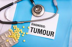 Tumour word written on medical blue folder with patient files, pills and stet Stock Photos