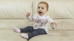 Child / baby girl eating and playing with a colorful ball on the sofa  Stock Footage
