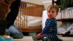 Adorable little boy in pajamas plays with a toy police car on the floor Stock Footage