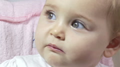 Very beautiful little girl with big eyes sitting on the stroller   Stock Footage