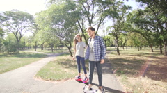 Young couple ridding hoverboard with holding hands. Wide shot Stock Footage
