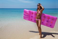 Brunette woman sunglasses sunbathe with air mattress on tropic beach Stock Photos