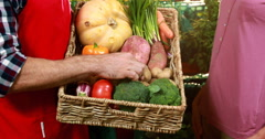 Male staff assisting a woman in shopping vegetables at organic section Stock Footage
