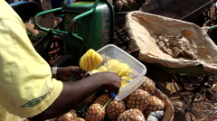 Street seller cutting pineapple in city market - Guinea Africa Stock Footage